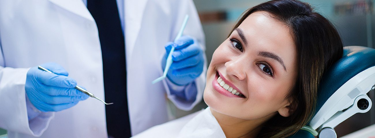smiling female patient receiving endodontic care from endodontist